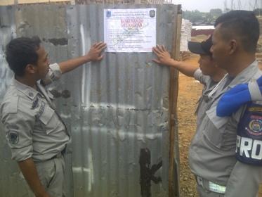 Petugas Satpol PP memasang stiker segel di Cluster Harvest Bintaro.(hen)