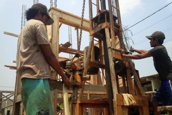 Pekerja membangun sumur bor di Setu. (one)