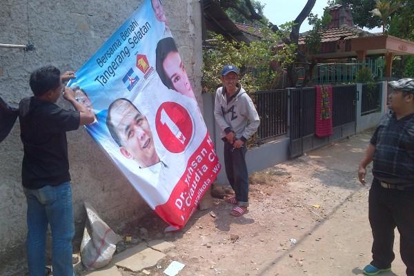 Alat peraga kampanye ilegal milik Ikhsan Modjo-Li Claudia diturunkan. (jok)