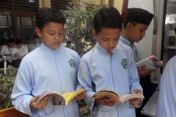 Muhamad Rafli Ramadhan, siswa VIII5 sedang membaca buku dari mobil perpustakaan keliling. (ist)