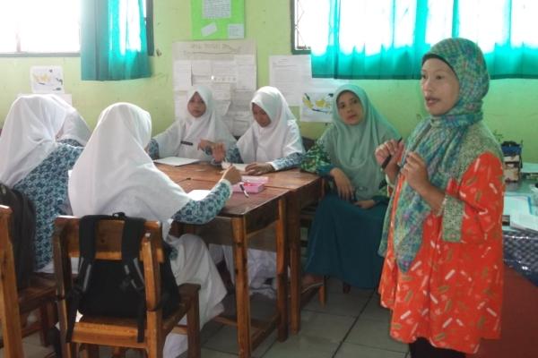 Ayu Cipta, wartawati sedang tampil mengajar di depan siswa. (ist)
