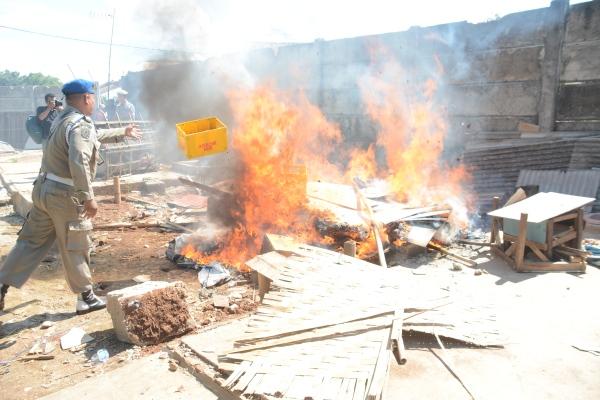 Petugas membakar bangunan warung remang-remang di kawasan Setu. (one)
