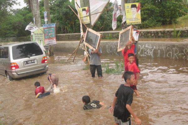 Anak-anak bermain di genangan banjir di Pondok Aren, Kota Tangsel. (hen)