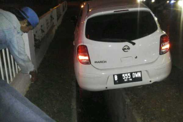 Nissan March terperosok ke parit setelah menyerempet pengemudi Gojek. (pay)