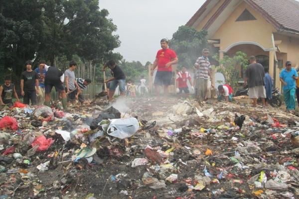 Warga Pondok Aren membersihkan sampah. (one)