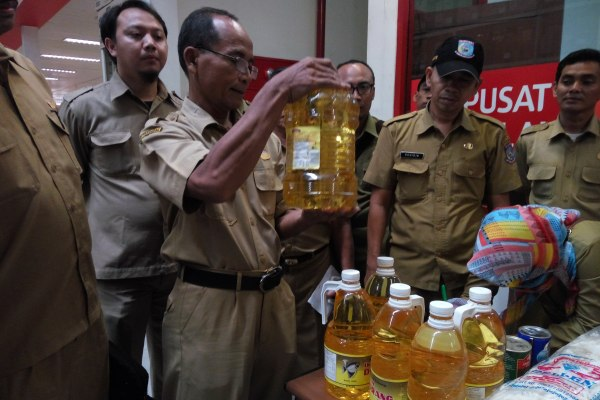 Petugas memeriksa minyak goreng kadaluarsa yang ditemukan di LotteMart Serpong. (man)