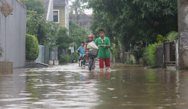 Warga melintasi genangan air di Perumahan Bukit Pamulang Indah, Tangsel. (dok)