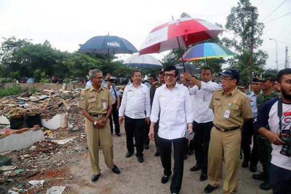 Mekum HAM Yasonna Laoly dipayungi saat kunjungan ke Kota Tangerang. (ist)
