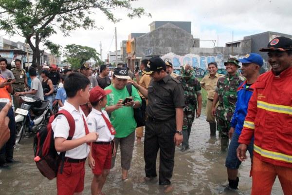 Walikota Tangerang berbincang dengan warga saat menungjungi lokasi banjir di Karawaci. (ist)