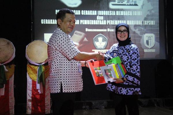 Rifki-Rosyad-Koordinator-Provinsi-Banten-USAID-PRIORITAS-menyerahkan-secara-simbolis-hibah-buku-bacaan-berjenjang-kepada-Bupati-Lebak-Iti-Oktavia. (ist)