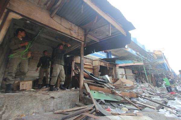 Petugas membongkar bangunan di trotoar depan Pasar Ciputat. (san)