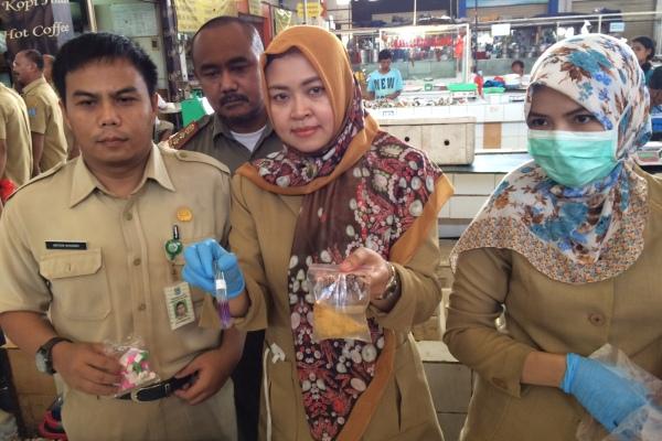 Kepala Labkesda, Latifah (tengah) menunjukkan hasil uji lab tahu goreng yang mengandung formalin. (man)
