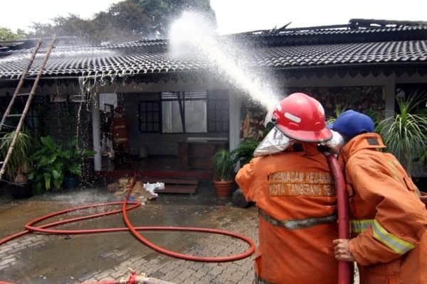 Petugas pemadam kebakaran kota Tangsel berusaha memadamkan sisa api yang membakar gedung di Pamulang. (dok)