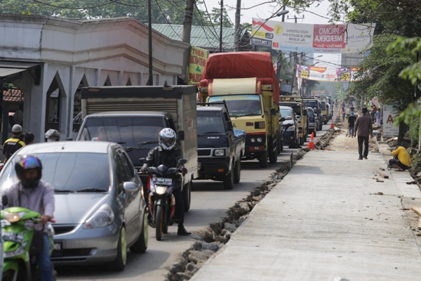 Pengendara melintasi ruas Jalan Buaran Viktor yang tengah betonisasi. (ist)