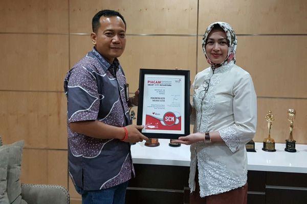 Walikota Tangsel saat menerima penghargaan dari PT Telkom. (nad)