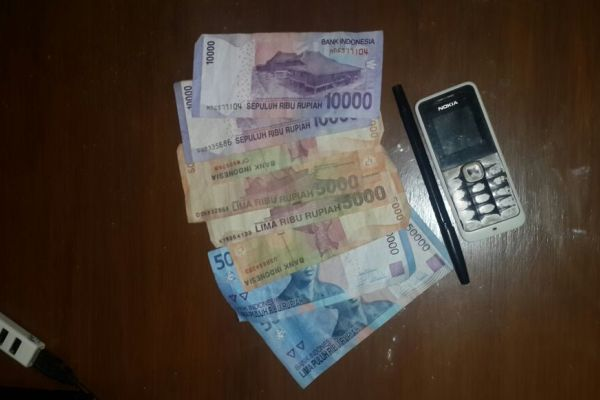 Barang bukti Polsek Balaraja, uang tunai dan handphone. (day)