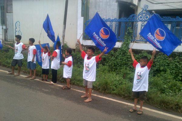 Anak-anak mengibarkan bendera partai pendukung salah satu paslon pada Pilkada Banten. (uad)