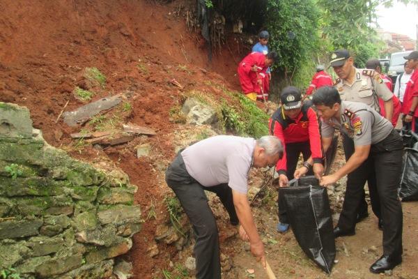 Kapolsek Pondok Aren, Kompol Indra (kanan) membantu evakuasi longsor di Pondok Pucung. (hen)