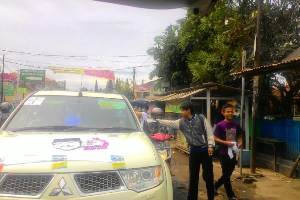 Warga menerima kaos dari tim kampanye pasangan Wahidin Halim-Andika Hazrumy. (uad)