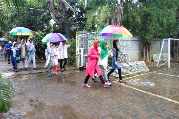 Peserta IMSO 2016 diguyur hujan saat kunjungan ke SDI Al-Ikhlas. (pp)